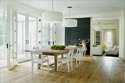G room wide plank natural wood floors chalk board wall farmhouse farm table white open back chairs drum shade ceiling light pendants fixtures french doors